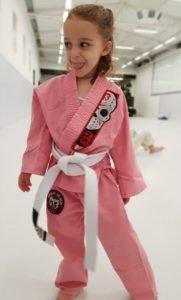 Menina feliz vestida para o jiu jitsu